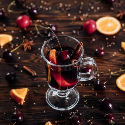 Mulled wine with a dynamic splash, spices and fruits on wooden background
