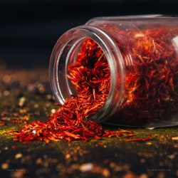 Saffron spice in an open glass jar on dark black background. Seasonings for food. Close-up.
